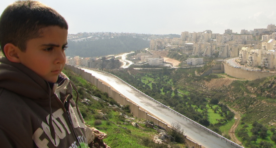 Emad's son Gibreel looks over at the Israeli settlements.