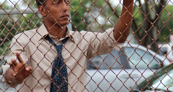 Byrd (Andre Royo) standing by the fence of the basketball court.
